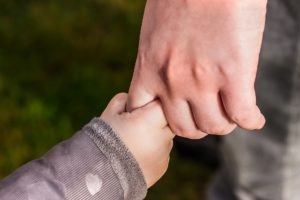 Kind hält Hand eines Erwachsenen